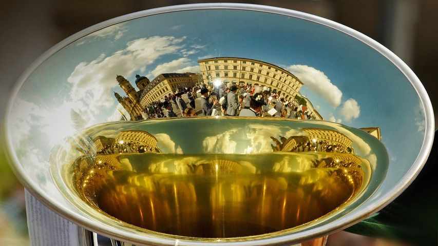 A marching band is reflected in the bell of a horn during the annual festival in Munich, Germany