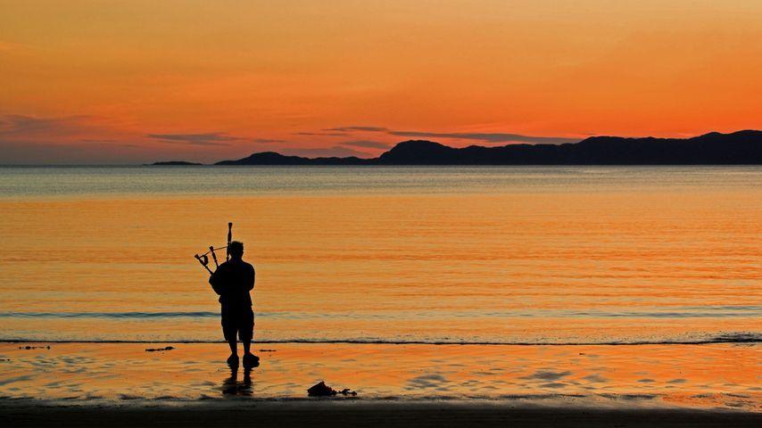 A bagpiper on Arisaig beach in Scotland