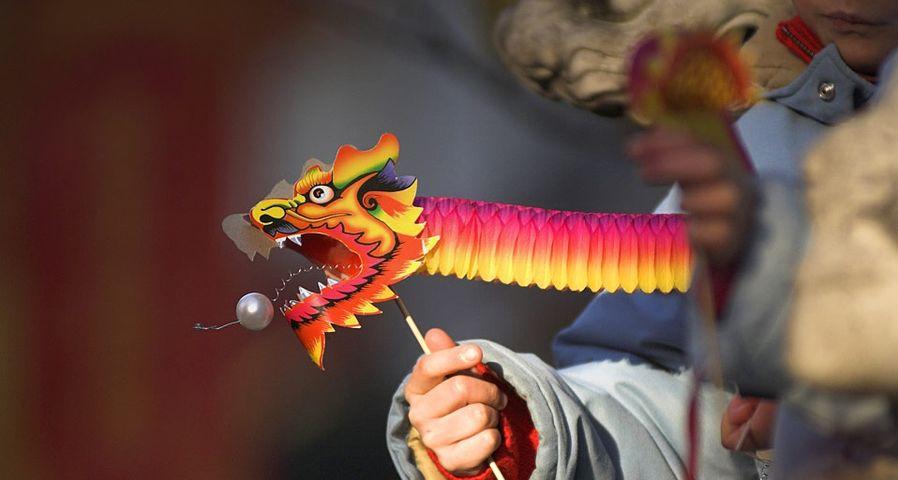 在伦敦庆祝中国新年的小朋友手中拿着纸龙