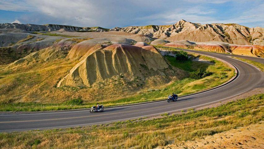 Des motards sur une route du Parc national des Badlands, Dakota du Sud, États-Unis