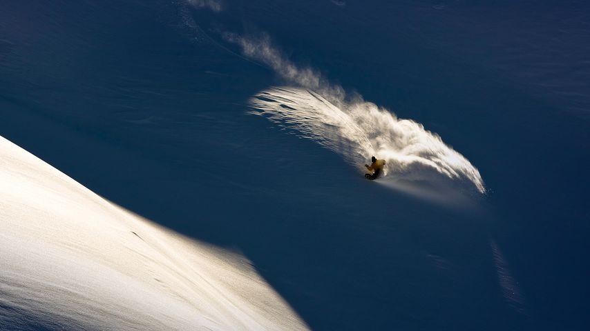 Snowboarder makes powder turn in backcountry terrain