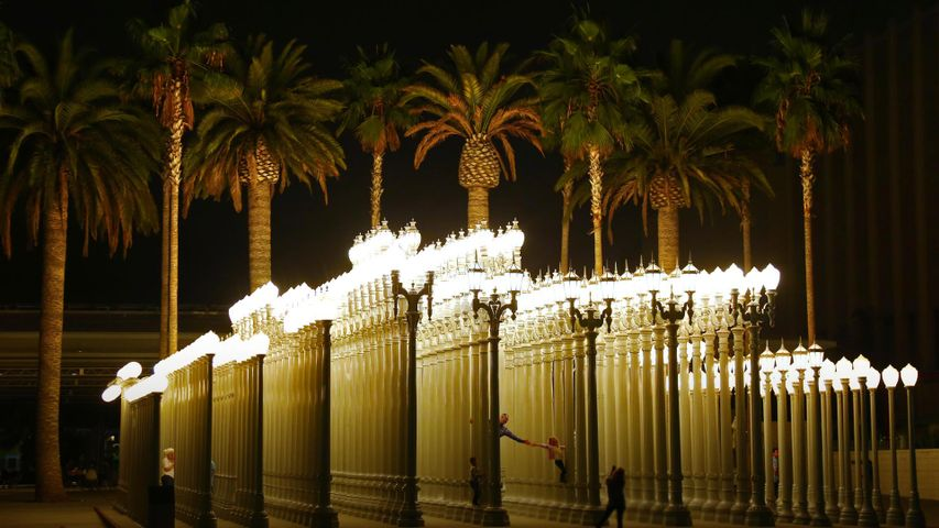 People in the 'Urban Light' sculpture by Chris Burden at LACMA in Los Angeles, California, USA