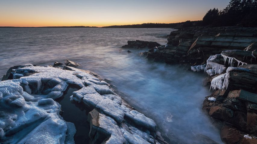 Thick ice clings to the Atlantic coast of Nova Scotia in twilight