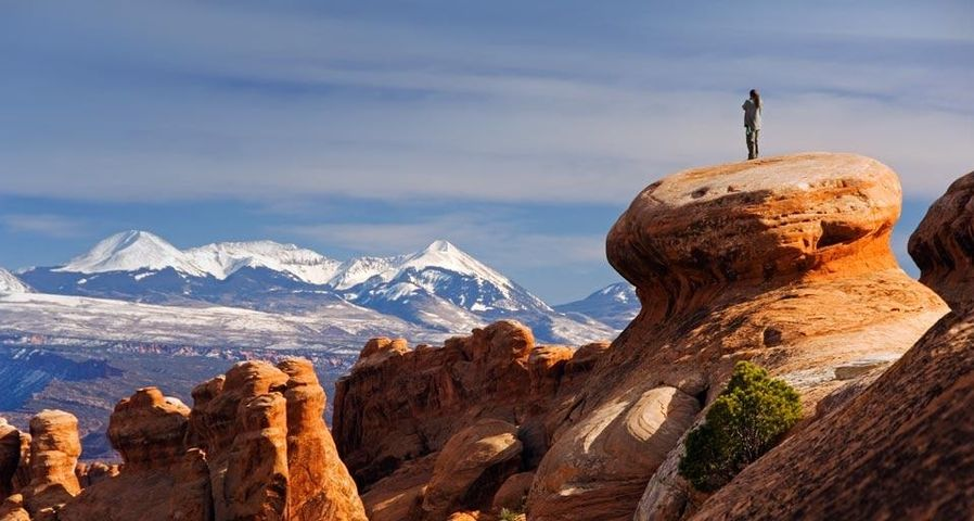 The snow-capped La Sal Mountains behind sandstone pinnacles at Devils Garden in Arches National Park, Utah, USA
