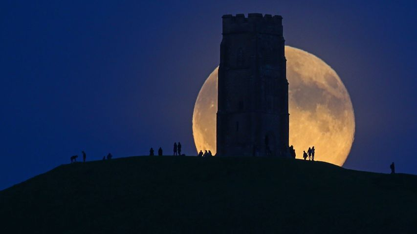 The moon rises over Glastonbury Tor, England