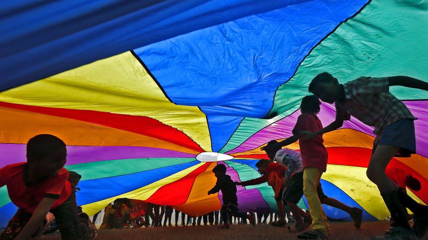 Children play under a parachute in Kolkata, India, for International Day of Friendship