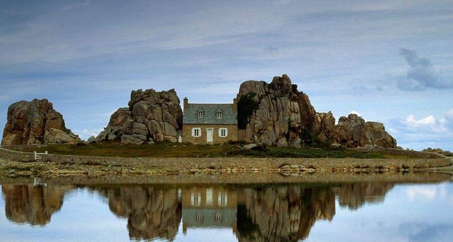 House between rocks is reflected in Brittany, France