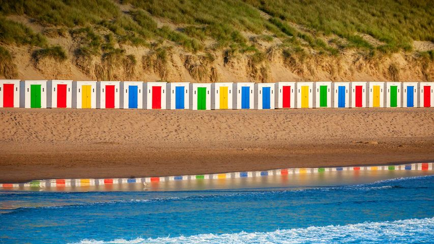 Beach huts reflecting in the water at Woolacombe Beach, Devon