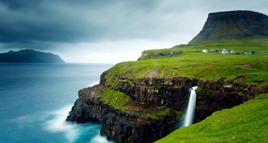 Village of Gásadalur below Heinanova mountain, with waterfall cascading over cliff into the Atlantic Ocean, Vágar, Faroe Islands