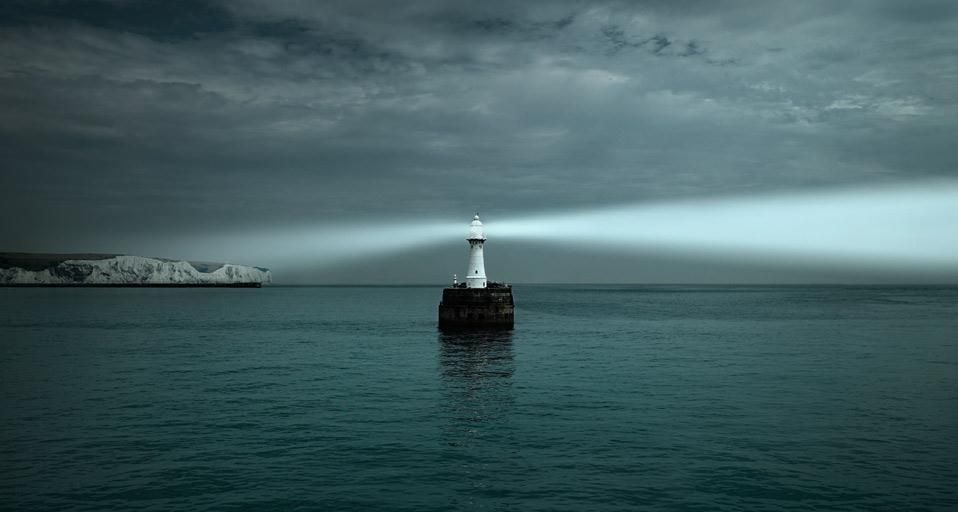 Lighthouse shining on White Cliffs of Dover and the English Channel
