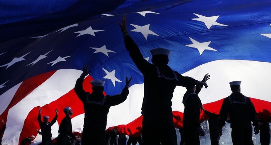 Military personnel stand under a huge American flag preceding a San Diego Chargers football game, San Diego, Calif.