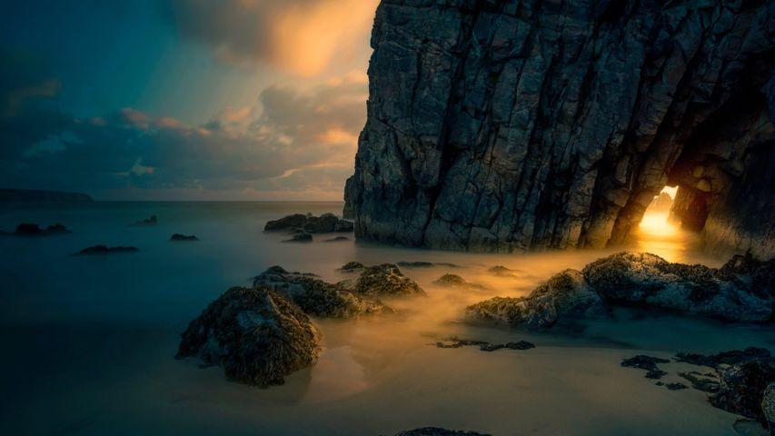 Light from sunrise through a sea cave on the Isle of Skye, Scotland