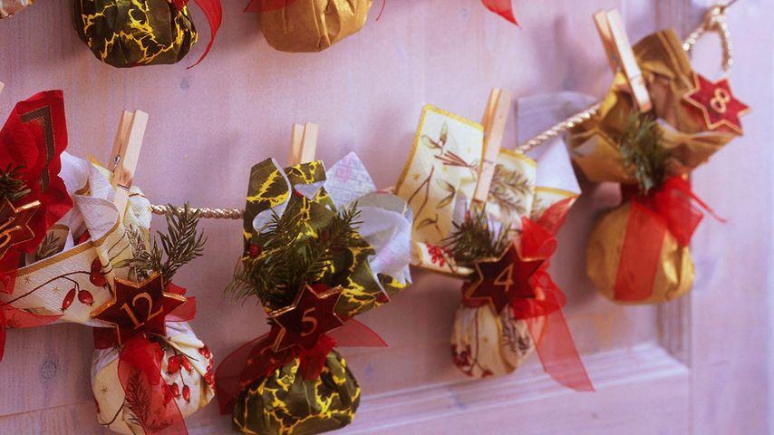 Adventskalender mit kleinen, aus Servietten gefalteten Säckchen