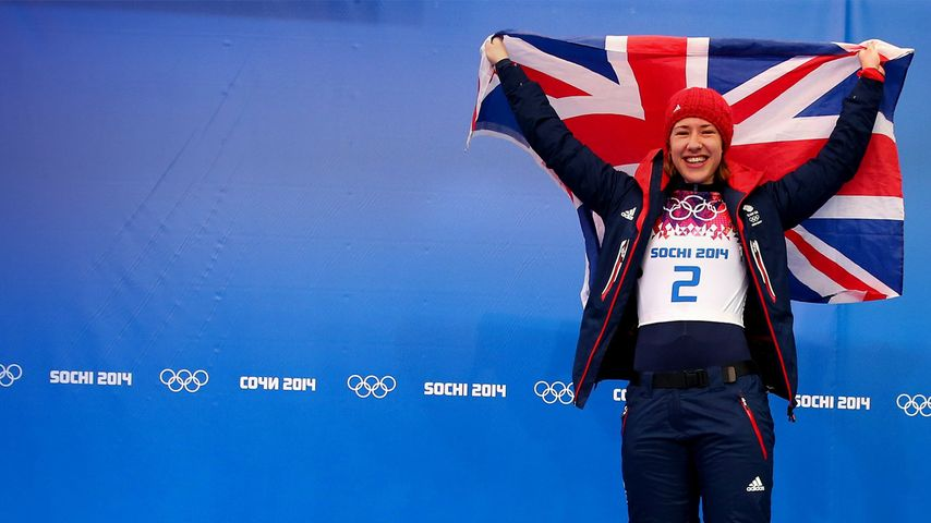 Gold medalist Lizzy Yarnold of Great Britain celebrates on the podium during the flower ceremony for the Women's Skelton on Day 7 of the Sochi 2014 Winter Olympics at Sliding Center Sanki on February 14, 2014 in Sochi, Russia