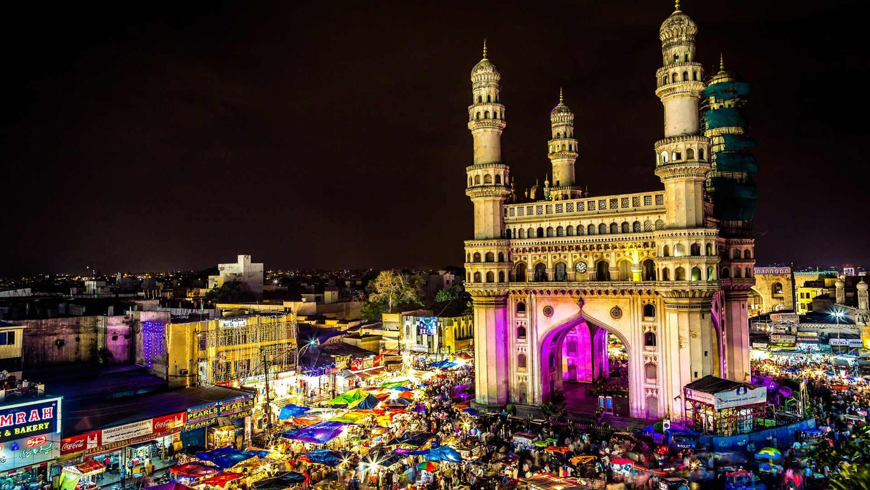High angle view of illuminated Charminar amidst market at night.