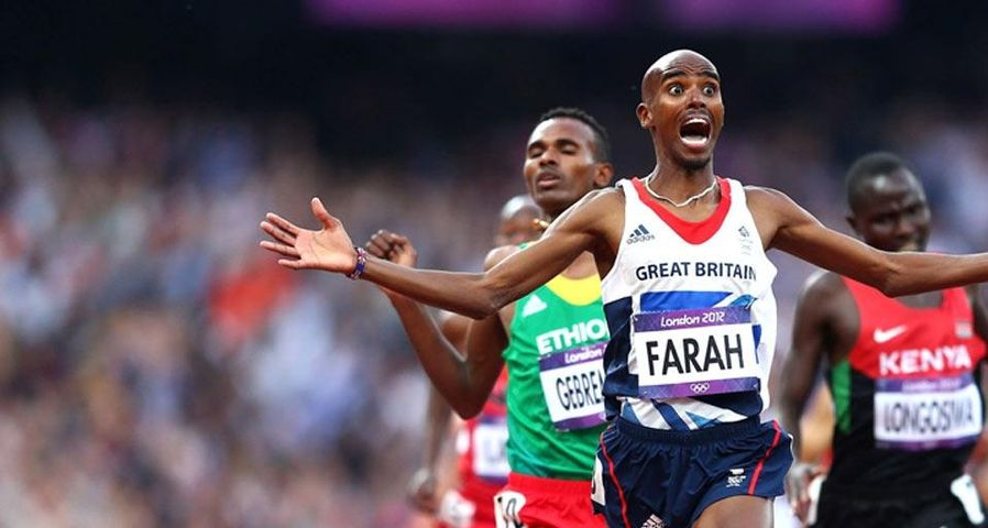 Mo Farah crosses the finish line to win gold in the Men's 5000m Final, London, England