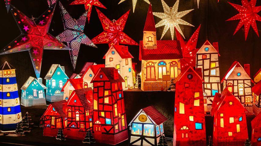 Leuchtende Papierhäuschen and Weihnachtssterne auf einem Weihnachtsmarkt in Hannover, Niedersachsen