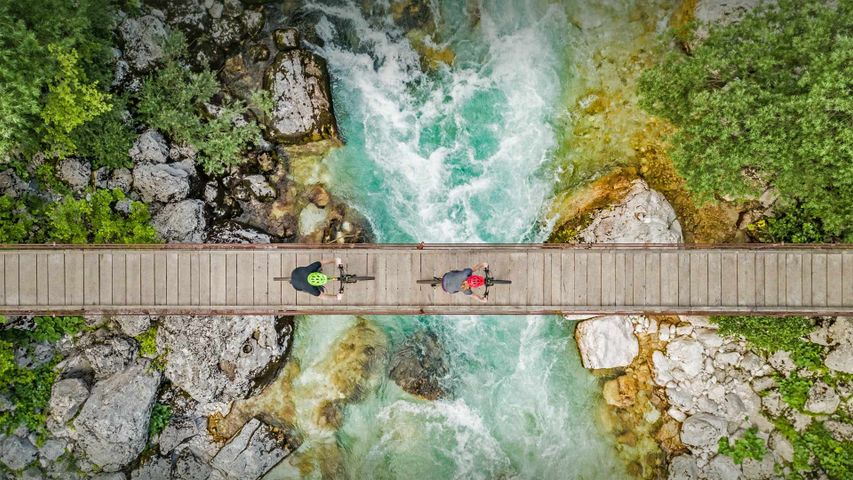 Aerial view of cyclists on a wooden suspension bridge over the river Soča in Slovenia