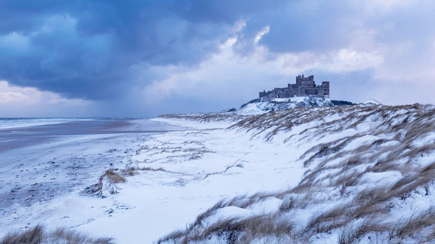 Bamburgh Castle and sand dunes after snowfall in Northumberland