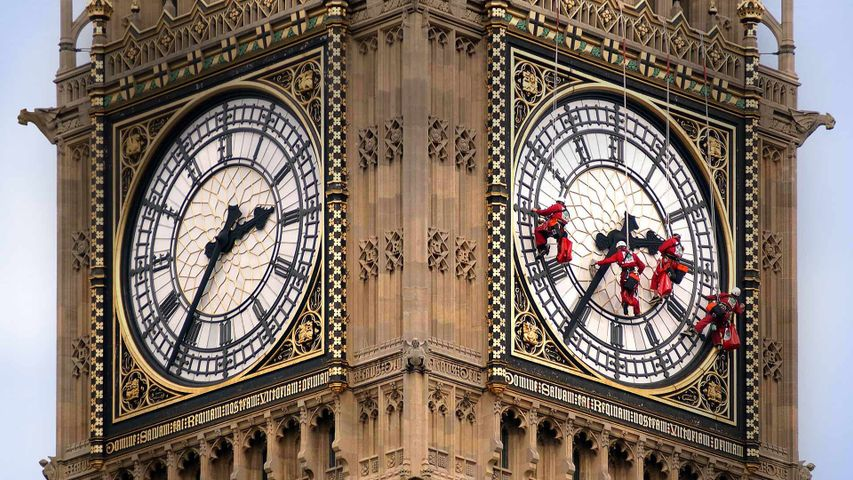 Workers cleaning the clock face of Big Ben in London, England