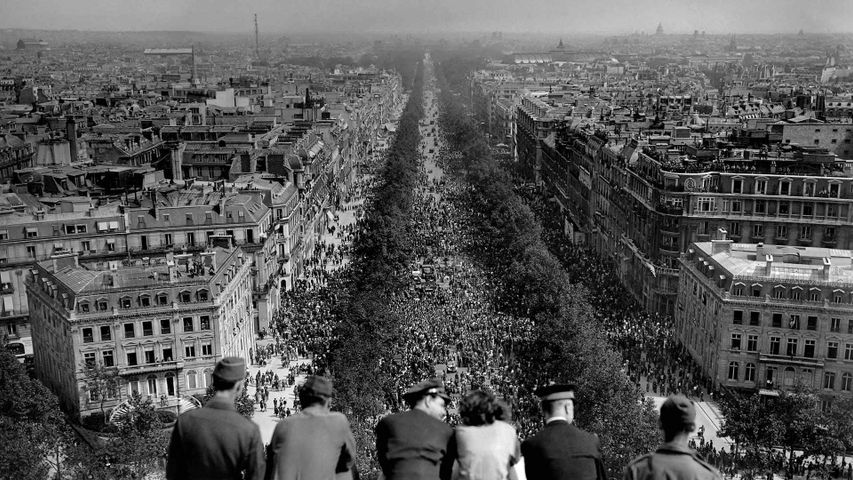 People looking at the crowded Avenue des Champs-Élysées from the Arc de Triomphe on May 8, 1945, Paris, France