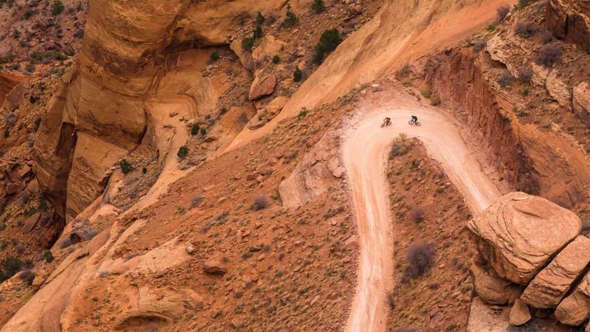 Two mountain bike riders make their way down the Shafer Trail switchbacks on White Rim Road in Canyonlands National Park, Utah