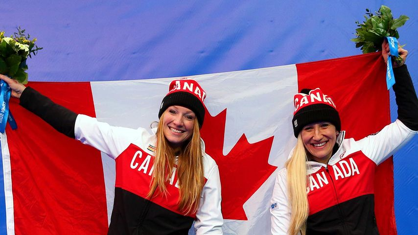 Kaillie Humphries (R) and Heather Moyse of Canada team 1 celebrate during the flower ceremony after winning the gold medal