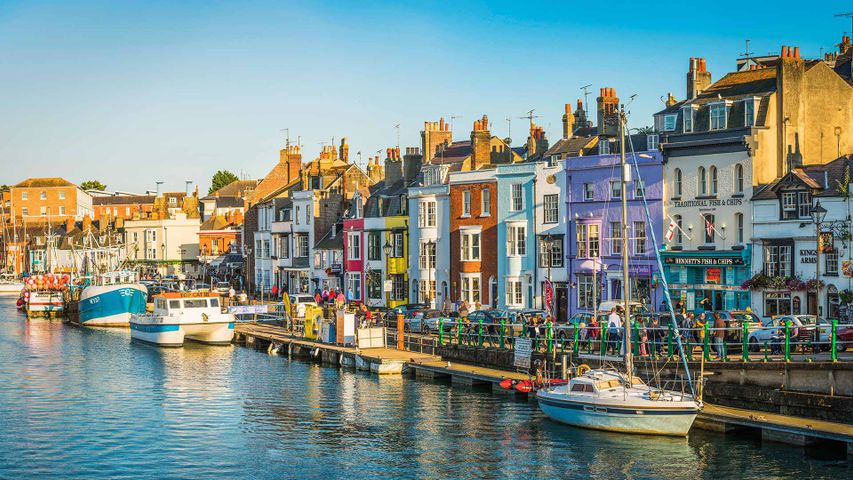 Colourful cottages, fishing boats and yachts around the harbour in Weymouth, Dorset