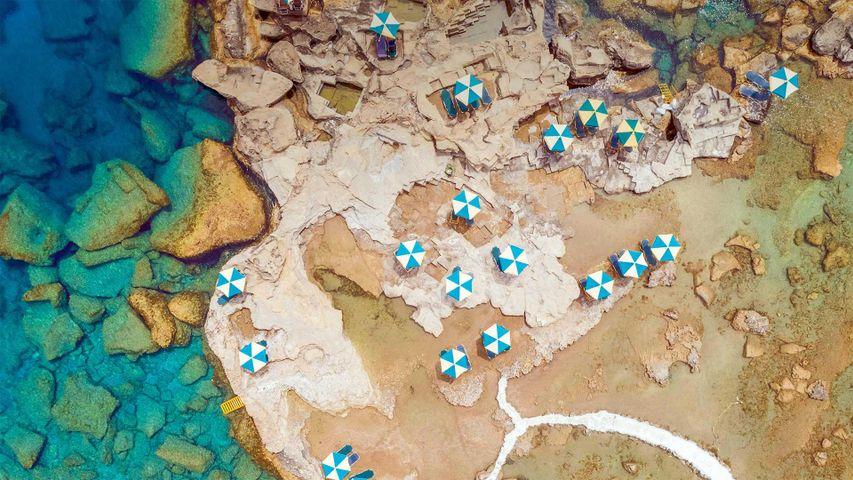 鸟瞰希腊罗德岛岩石海岸上蓝白相间的遮阳伞