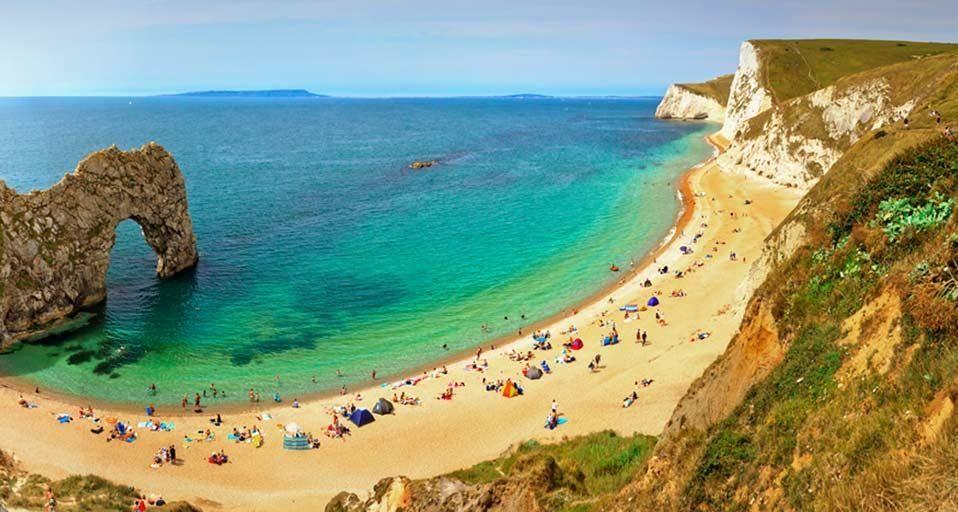 People enjoying the seaside at Durdle Door near Lulworth along the Jurassic Coast, Dorset, England