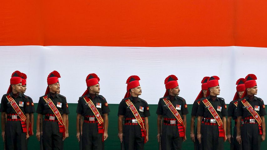 Soldiers stand guard in front of a tricolour flag rehearsal
