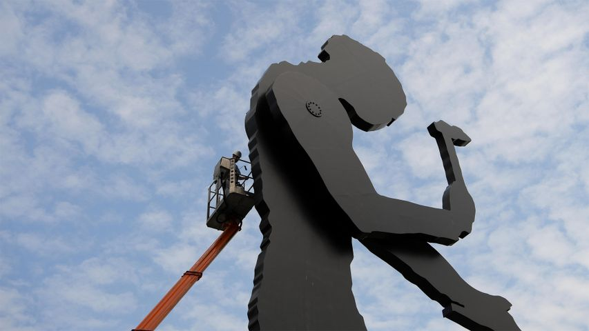A worker painting the Hammering Man, a sculpture by Jonathan Borofsky, in Frankfurt, Germany