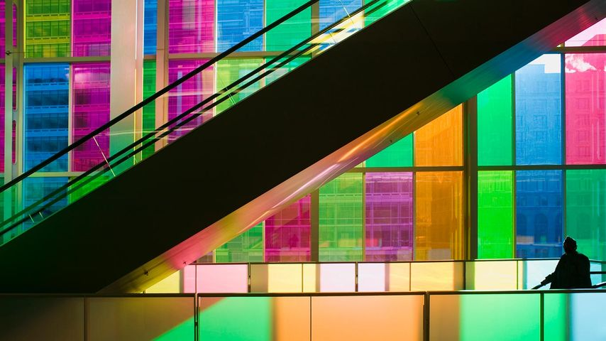 Silhouetted man standing in front of multi-coloured glass windows of Montreal's Palais des Congres Montreal, Quebec, Canada