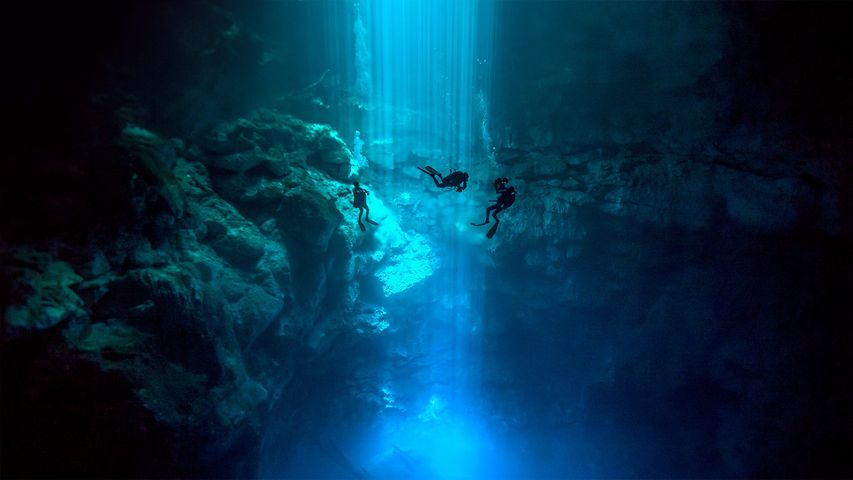 Divers at El Pit Cenote, located in Dos Ojos Natural Park, Quintana Roo, Mexico