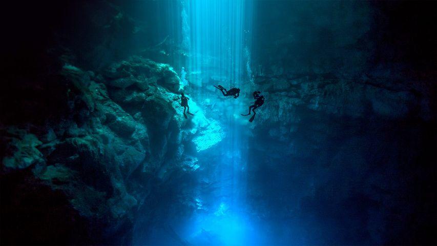 Divers at El Pit cenote, located in Sistema Dos Ojos, Quintana Roo, Mexico