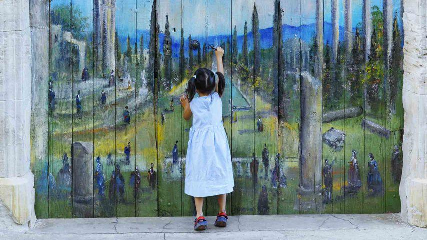 Une jeune passionnée d'art devant une porte peinte, Roussillon, Provence-Alpes-Côte d'Azur.