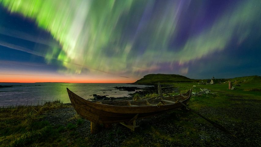 The Northern Lights over a rowboat in Norstead Viking replica village in Newfoundland