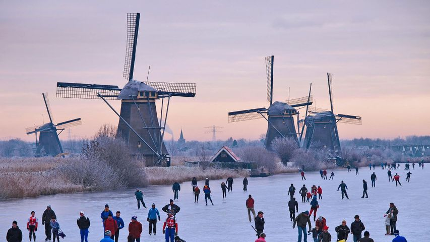Skating on a frozen canal near the windmills at Kinderdijk in the Netherlands
