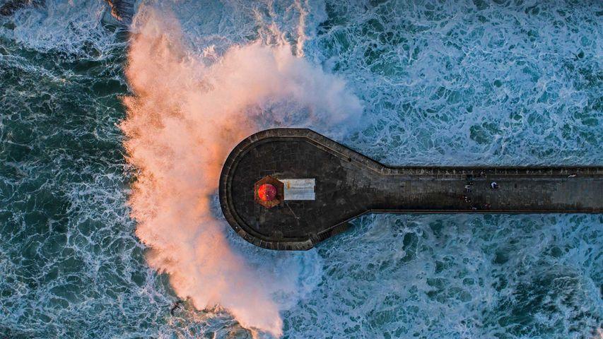 Wave crashing on Farolim de Felgueiras, a lighthouse in Porto, Portugal