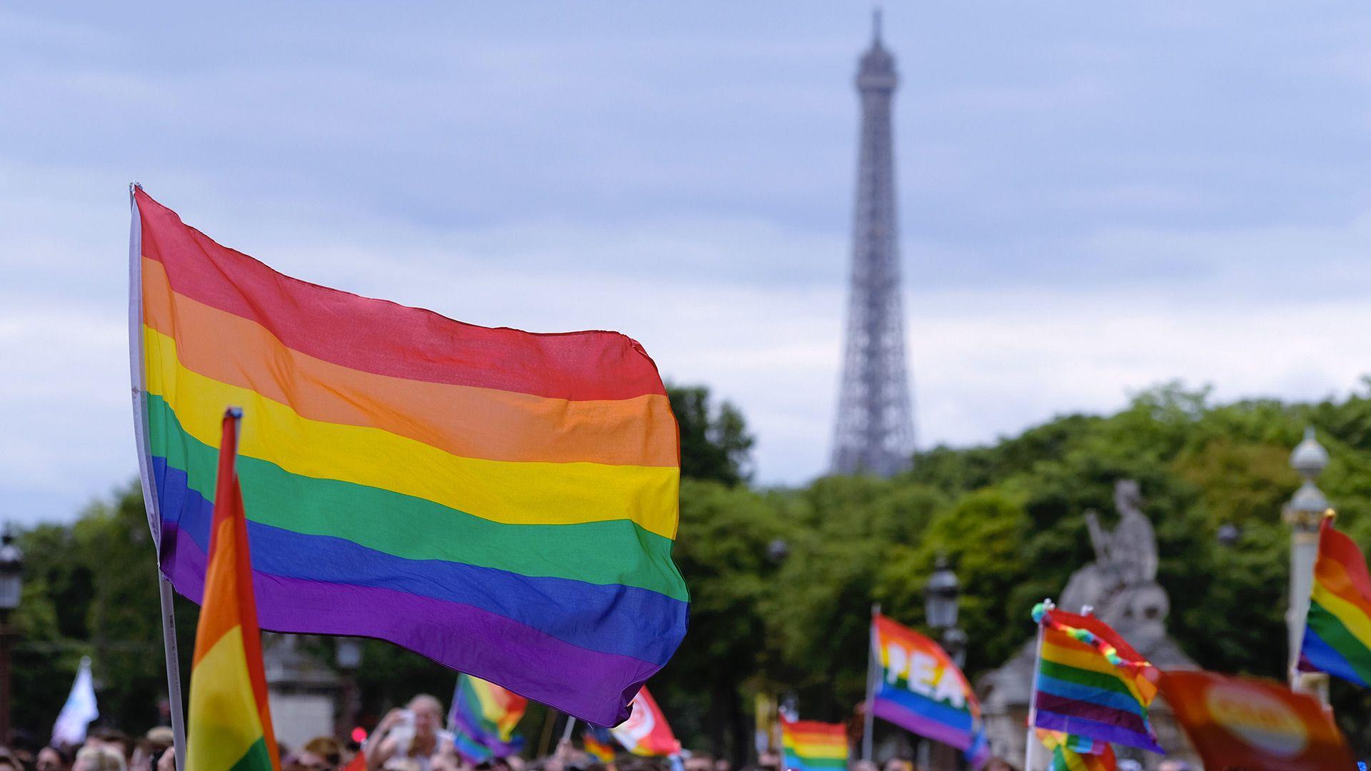 Drapeau arc-en-ciel flottant près de la Tour Eiffel lors de la Marche des fiertés de Paris