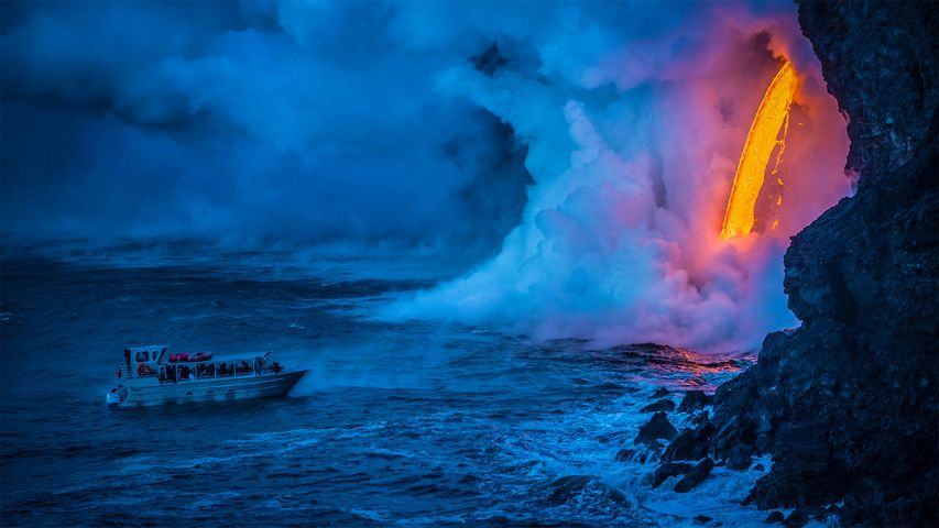 A lava flow hits water as a tour boat passes, Hawaii Volcanoes National Park