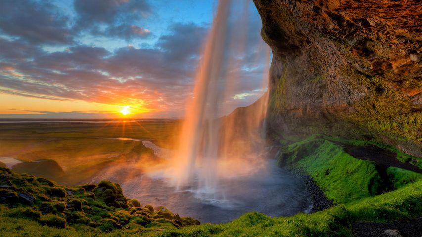 Le soleil de minuit derrière la cascade Seljalandsfoss près de la côte sud de l'Islande