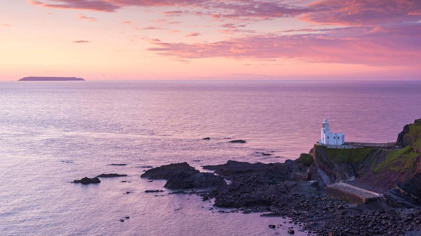 Hartland Point Lighthouse and Lundy Island beneath a colourful sunset, North Devon