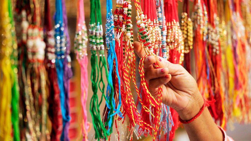 Woman shops for 'rakhis' in a market ahead of Raksha Bandhan.