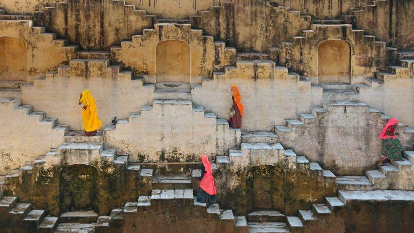 Einheimische Frauen auf den Treppen eines Stufenbrunnens in der Nähe des Amber-Forts in Jaipur, Rajasthan, Indien