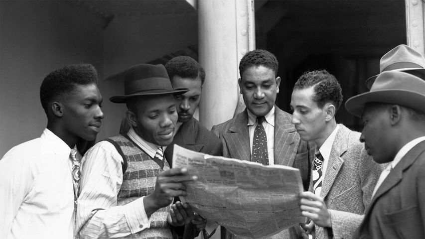Reading the news aboard the Empire Windrush on arrival at Tilbury, Essex on 22 June 1948