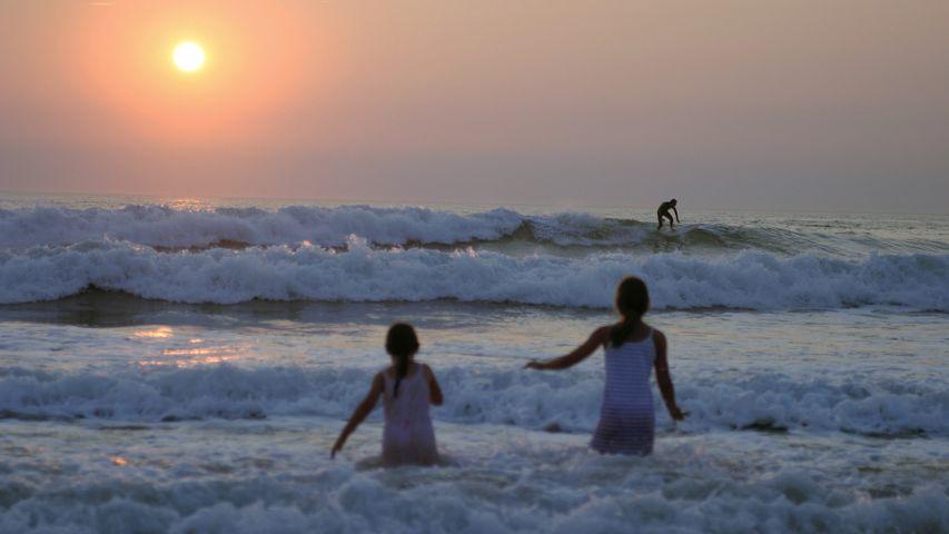 Deux fillettes en pleine baignade devant un coucher de soleil à Lacanau, France