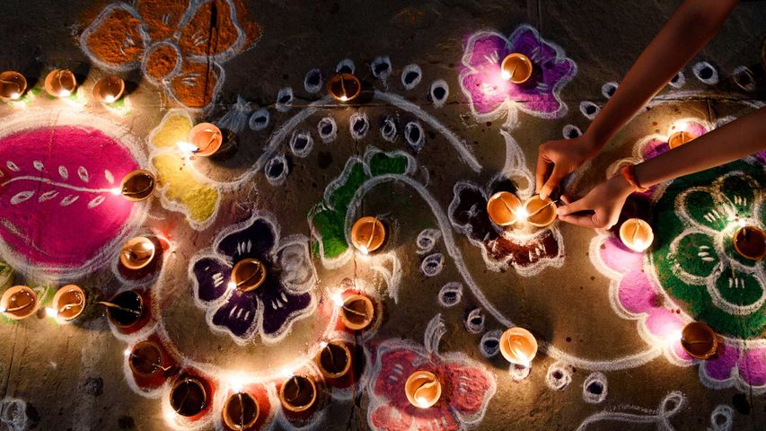 Oil lamps being arranged on rangoli designs during Diwali