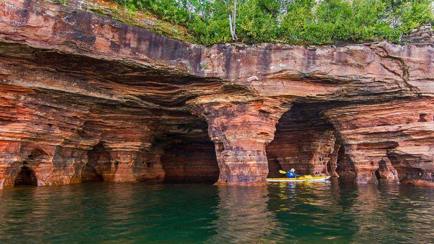 Kayaker exploring sandstone sea caves in Apostle Islands National Lakeshore near Bayfield, Wisconsin