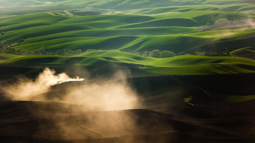 A tractor kicks up dust while tilling fields on the Palouse near Pullman, Washington